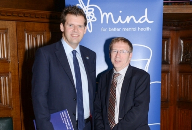 Ben Howlett MP standing in front of a Mind poster